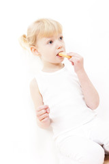 portrait of little girl eating buscuit
