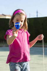 Little girl playing with a spinning top