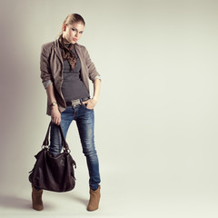 Glamour pretty girl holding stylish leather bag in studio