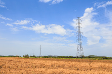 Electricity transmission pylons in the rural area with blue sky