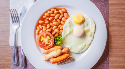 English breakfast with fried egg, sausages, tomato and bean
