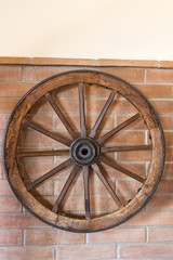 Antique Cart Wheel hanging on a wall.