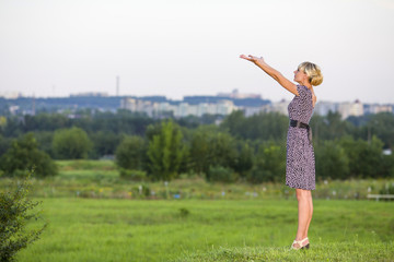 woman costs in field having extended hands forward