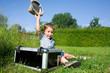 canvas print picture - kleiner Junge mit einem Koffer auf einer Wiese