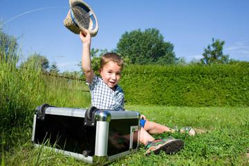 kleiner Junge mit einem Koffer auf einer Wiese
