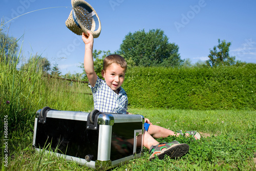 canvas print picture kleiner Junge mit einem Koffer auf einer Wiese