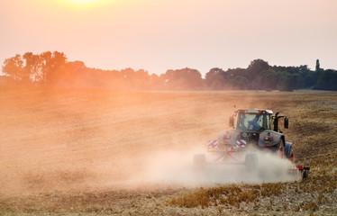 Traktor orzący pole podczas zachodu słońca