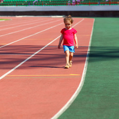 little girl child involved in athletics at the stadium
