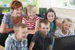 Group Of Elementary Pupils In Computer Class With Teacher