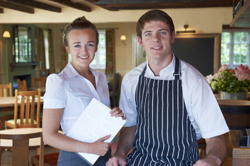 Portrait Of Chef And Waitress In Restaurant