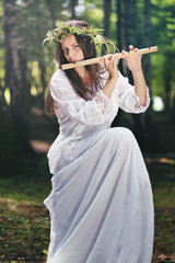 Beautiful woman playing a flute in the woods