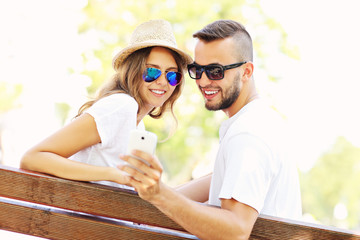 Young couple on a bench with smartphone