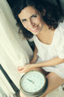 beautiful woman holding a big clock