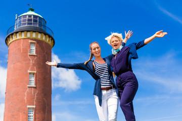 Freundinnen stehen am Leuchtturm