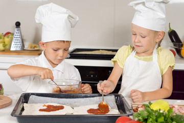 Young children making themselves a homemade pizza