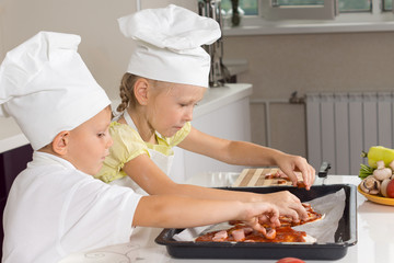 Young girl and boy loading ingredients onto pizza