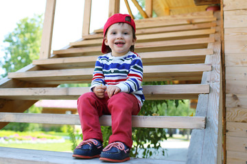 happy baby sitting on stairs outdoors