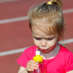 Little baby girl carries water in a bottle at the stadium
