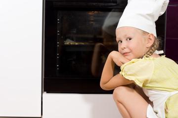 Little girl watching her homemade pizza cook
