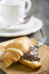 Croissant with chocolate on a sheet of parchment.
