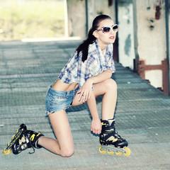 fashionable girl in sunglasses on roller skates.