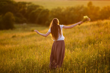 Happy woman in the field with a bouquet of flowers