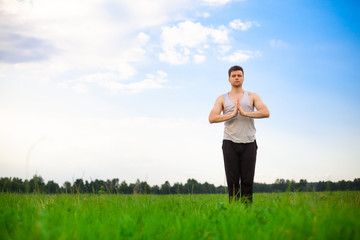 Young man doing yoga in park