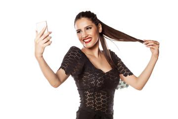 smiling girl make selfie and holding her hair