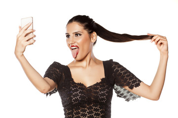 Funny girl make selfie and loll tongue