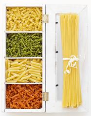 Espaguetis y macarrones de distintos colores en caja de madera