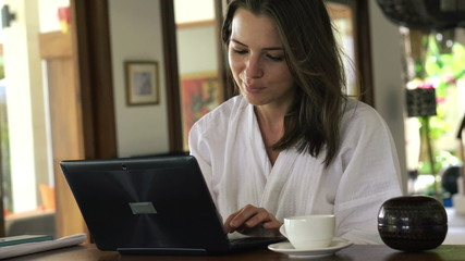 Attractive woman in bathrobe working on laptop at home