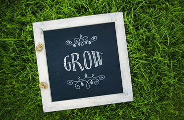 "inspirational chalk board on the grass with word ""Grow"""
