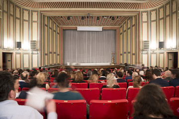 Motion blurred image of classic theater with people