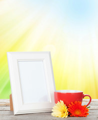 Photo frame with cup of coffee and gerbera flowers