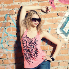 fashionable girl  posing on background of  wall with graffiti