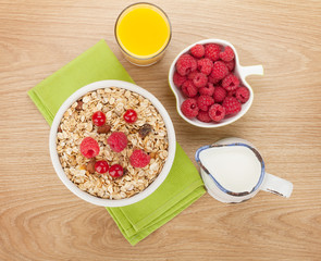 Healty breakfast with muesli, berries, milk and orange juice