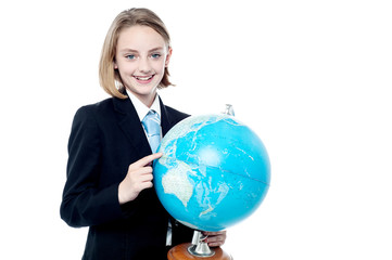 Business girl indicating a place in globe map