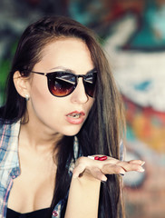 Beautiful young girl in sunglasses is going to swallow pills.