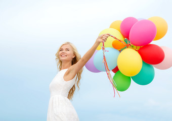 smiling woman with colorful balloons outside