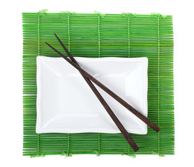 Chopsticks and utensils over bamboo mat