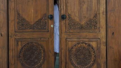Woman opening wooden door of luxury villa, super slow motion