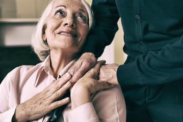 Senior woman on wheelchair taking her husband's hand