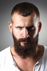 Portrait of handsome bearded man standing, isolated on grey