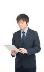 Worried asian businessman looking at company results on his tabl