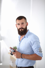 Young beard man holding a camera while standing against white