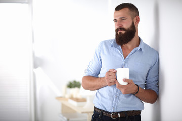 Young man  standing near wall and holding cup of coffee in