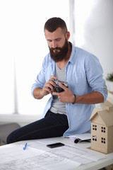 Portrait of male designer sitting on a table with blueprints and