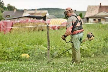 jardinier avec une tondeuse à essence