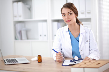 Beautiful young smiling female doctor sitting at the desk and