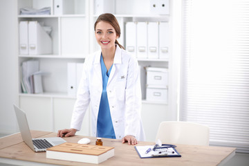 Young doctor woman standing near table in hospital